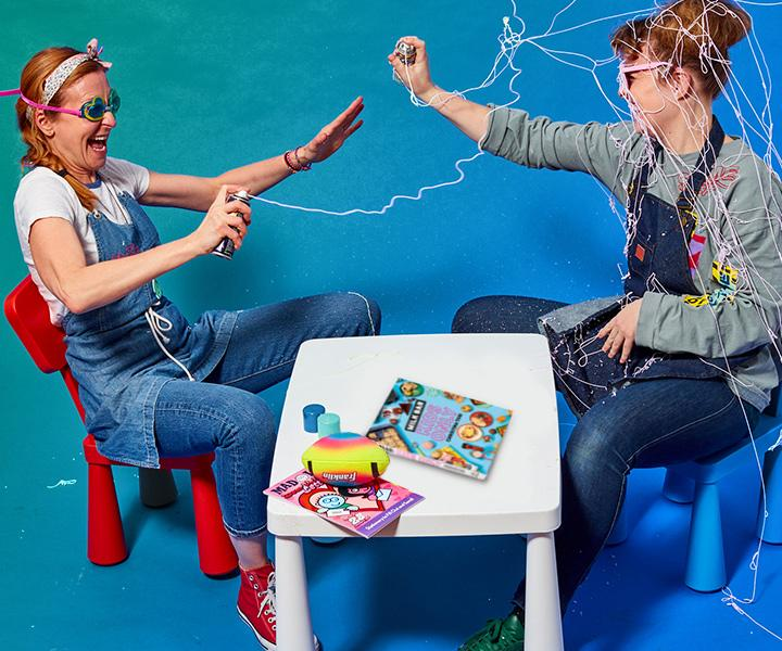 Christina Tosi and her friend sit in kids chairs at a kids table with the toys scattered around the Milk Bar: Kids Only cookbook on the table while they shoot each other with silly string.