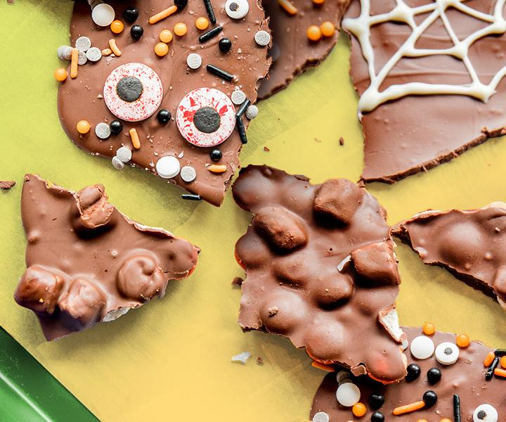 Scattered pieces of chocolate Boo Bark with black and orange sprinkles, candy eyeballs, and mini pretzels on a green and yellow surface. A play button is overlaid on the thumbnail.