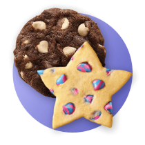 A chocolate cookie with white morsels and a star shaped cookie with unicorn vanilla morsels against a royal blue gradient circle.