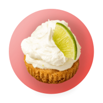 A mini lemon lime tartlet topped with lemon lime cream cheese and a lime wedge against a light pink gradient circle.