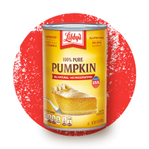 Front view photograph of an orange and yellow can of Libby's 100% Pure Pumpkin on a distressed bright red circle. It has the Libby's name and red and white logo above the product name and a slice of pumpkin pie on a silver serving spatula.