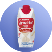 Front view of photograph of an octagonal carton of Lactose-Free Evaporated Milk in a blue circle. It has the Carnation logo on it, a red plastic bottle cap, and an image of evaporated milk pouring onto a white spatula.