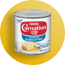 Front view photograph of a can of Carnation Sweetened Condensed Milk on a yellow circle. The can has a light blue label and an image of a lemon bar.
