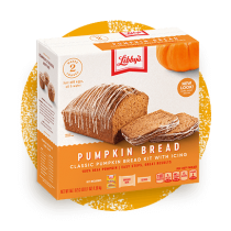 Front view photograph of a light orange and brown box of Libby's Pumpkin Bread Kit on an orange distressed circle. It has the Libby's name and red and white logo above two loaves and two slices of pumpkin bread and a dark orange and white label that features the product name in white under an illustrated pumpkin.