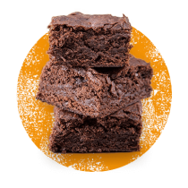 Photograph of 3 pieces of pumpkin chocolate brownies stacked in front of a distressed orange circle.