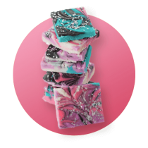 A tall stack of Galaxy Fudge with swirling blue, brown, and pink chocolate and vanilla topped with sprinkles against a pink gradient circle.