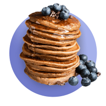 A tall stack of pancakes topped with fresh blueberries that spill off to the side against a royal blue gradient circle.
