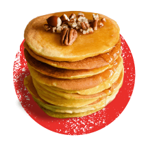 A tall stack of pancakes topped with whole pecans and hazelnuts on a distressed red circle.