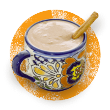 A colorful mug filled to the brim with pumpkin hot cocoa and a cinnamon stick on a distressed orange circle.