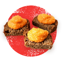 Photograph of 3 slices of bread topped with pumpkin puree in front of a distressed orange circle.