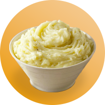 A white bowl filled with creamy mashed potatoes in front of an orange circle.