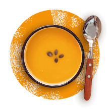 Overhead photograph of a spoon beside a brown bowl of pumpkin soup garnished with pumpkin seeds in front of a distressed orange circle.