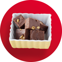 A square white dish filled with 5 fudge squares with nuts in front of a red circle.