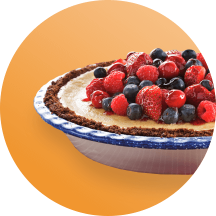 A cream pie in a metal pie pan piled high with fresh strawberries, raspberries, and blueberries in front of an orange circle.