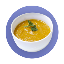 A white bowl filled with creamy pumpkin soup garnished with coriander against a purple gradient circle.