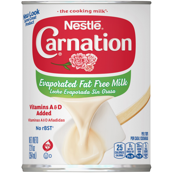 Front view photograph of a can of Evaporated Fat Free Milk in the colors of white, red, and blue. It has the Carnation name and flower logo on it, a dark blue plastic bottle cap, and an image of evaporated milk pouring onto a white spatula.