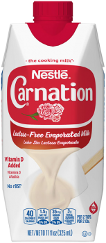 Front view of photograph of an octagonal carton of Lactose-Free Evaporated Milk in the colors of white and red. It has the Carnation name and flower logo on it, a red plastic bottle cap, and an image of evaporated milk pouring onto a white spatula.